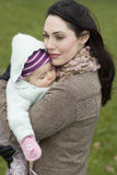 Mother With Baby Sleeping In Her Arms Stock Images