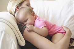 Mother With Baby Sleeping On Sofa Stock Image