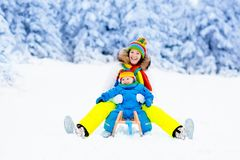 Mother and baby on sleigh ride. Winter snow fun. Stock Photos