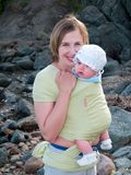 Mother with baby in sling. Family resting together on seaside showing happy mother with baby in the sling Royalty Free Stock Images