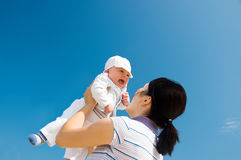 Mother and baby smiling. Baby in mother's arms on blue sky background stock photo