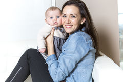 Mother with baby on the sofa taking good time Royalty Free Stock Photos