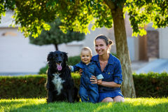 Mother with baby son and black dog in green neighborhood Royalty Free Stock Photography