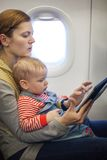 Mother and baby son on board of airplane Stock Image
