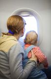 Mother and baby son on board of airplane Royalty Free Stock Photo