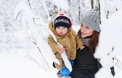 Mother and baby son embracing in a winter park amoung trees branches. Mother and little boy in her arms. Happy family. Childhood and parenthood happiness royalty free stock photos