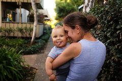 Mother with baby son in green neighborhood Stock Images
