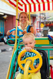 Mother with baby son have fun, riding on rental quadricycle. Happy family - mother with baby son have fun, riding on rental quadricycle along street of old Royalty Free Stock Photography