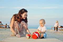 Mother and baby son playing toys. Near the sea Stock Images