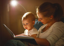 Mother and baby son reading a book in bed Stock Images