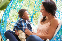 Mother With Baby Son Relaxing On Outdoor Garden Swing Seat royalty free stock photos