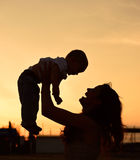 Mother and baby son silhouettes. On beach at sunset stock photography