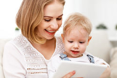 Mother and baby son with a tablet computer at home. Watching cartoons and playing Royalty Free Stock Photos