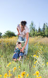 Mother and baby son taking a walk. Mother pushing her baby son in a stroller offering him a flower to play with Royalty Free Stock Photography