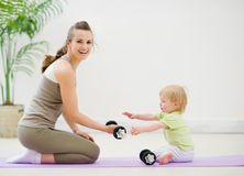 Mother and baby spending time in gym. Mother and baby girl spending time in gym royalty free stock photography