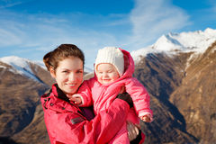 Mother with baby in sport outwear. With mountains in background Stock Images
