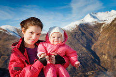 Mother with baby in sport outwear. With mountains in background Royalty Free Stock Photo