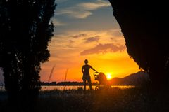 Mother with baby in stroller enjoying motherhood at sunset Royalty Free Stock Images