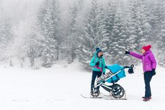 Mother with baby stroller enjoying winter forest with female friend or partner, family time. Hiking or power walking woman with stock images