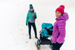Mother with baby stroller enjoying winter forest with female friend or partner, family time. Hiking or power walking woman with stock image
