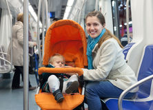 Mother with baby in stroller inside metro. Young mother with baby in stroller inside metro train Stock Image