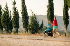 Mother with baby stroller running at sunset landscape Stock Photography