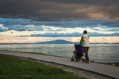 Mother with Baby Stroller Walking by the Sea Royalty Free Stock Photo