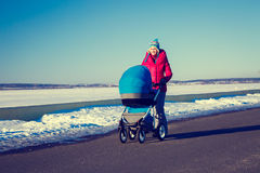 Mother with Baby Stroller Walking in Winter Park Stock Photo
