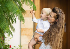 Mother and baby studying plants outdoors Stock Images
