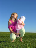 Mother with baby on sunset. Blue sky green grass stock photos