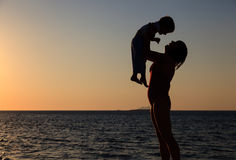 Mother and baby at sunset beach Stock Photos