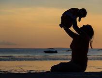 Mother and baby at sunset beach Stock Photography