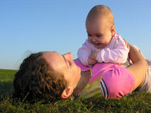 Mother with baby on sunset lie Royalty Free Stock Photography