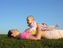 Mother with baby on sunset lie. From the side royalty free stock photography