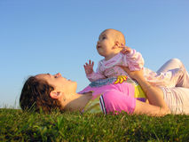Mother with baby on sunset lie. From the side royalty free stock photos