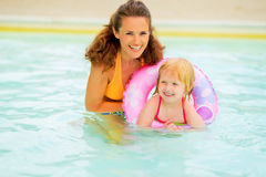 Mother and baby with swim ring swimming in pool. Portrait of happy mother and baby girl with swim ring swimming in pool Royalty Free Stock Image