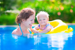 Mother and baby in swiming pool. Happy family, young active mother and adorable curly little baby having fun in a swimming pool, child learning to swim in an Stock Photography