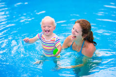 Mother and baby in swiming pool. Happy family, young active mother and adorable curly little baby having fun in a swimming pool, child learning to swim in an Stock Photo