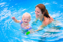 Mother and baby in swiming pool. Happy family, young active mother and adorable curly little baby having fun in a swimming pool, child learning to swim in an Stock Images