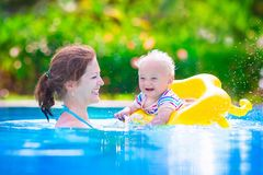 Mother and baby in swiming pool. Happy family, young active mother and adorable curly little baby having fun in a swimming pool, child learning to swim in an Stock Image