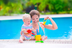 Mother and baby in swiming pool. Happy family, young active mother and adorable curly little baby having fun in a swimming pool, playing with toy watering can Stock Image