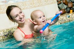 Mother and baby in swimming pool. Mother and baby child playing in a swimming pool. DOF focus on babys face with mother slightly defocused in the background stock photos