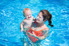 Mother and baby in swimming pool. Happy young mother and her little son, adorable laughing baby boy having fun together in an outdoor swimming pool on a hot Stock Photos