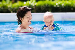 Mother and baby in swimming pool. Happy young mother playing with her baby in outdoor swimming pool on hot summer day. Kids learn to swim during family vacation Stock Images