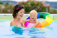 Mother and baby in swimming pool. Happy young mother playing with her baby in outdoor swimming pool on hot summer day. Kids learn to swim during family vacation Royalty Free Stock Photography