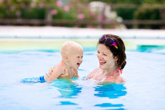 Mother and baby in swimming pool. Happy young mother playing with her baby in outdoor swimming pool on hot summer day. Kids learn to swim during family vacation Royalty Free Stock Images