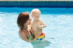 Mother and baby in swimming pool. Mother and baby in outdoor swimming pool of tropical resort. Kid learning to swim. Mom and child playing in water. Family royalty free stock image