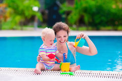 Mother and baby in a swimming pool. Mother and baby in swimming pool. Parent and child swim in a tropical resort. Summer outdoor activity for family with kids Royalty Free Stock Photography