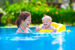 Mother and baby in a swimming pool. Mother and baby in swimming pool. Parent and child swim in a tropical resort. Summer outdoor activity for family with kids royalty free stock images