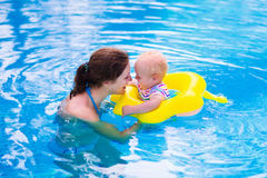 Mother and baby in a swimming pool. Mother and baby in swimming pool. Parent and child swim in a tropical resort. Summer outdoor activity for family with kids royalty free stock image